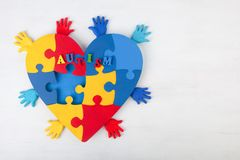 Puzzle heart hands support autism awareness. Puzzle heart hands on white wooden background support autism awareness Royalty Free Stock Photo