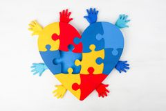 Puzzle heart hands support autism awareness. Puzzle heart hands on white wooden background support autism awareness Stock Images