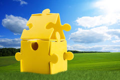 Puzzle house on meadow Stock Images