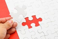 Puzzle inachevé avec le morceau absent sur la main humaine Images stock