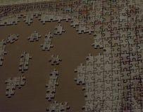 Puzzle inachevé de beaucoup de morceaux dans le processus et un carton comme fond photo stock