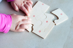 Puzzle in kid hand. Little child solving a puzzle Royalty Free Stock Image