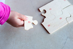 Puzzle in kid hand. Little child solving a puzzle Stock Photos