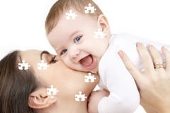 Puzzle of laughing baby playing with mother Stock Image