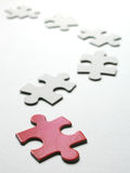 Puzzle - Looking for the right place. A red puzzle piece leading the rest Stock Images