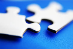 Puzzle macro. Closeup of two puzzle pieces fitting together Stock Photo