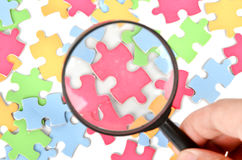 Puzzle and magnifier Royalty Free Stock Images