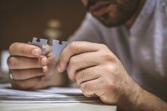 Puzzle in mano dell'uomo d'affari Concetto Fuoco a disposizione fotografie stock