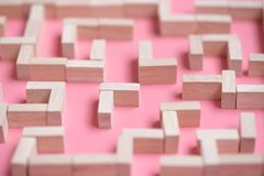 Puzzle maze wood block. On pink background Stock Photo
