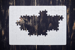 Puzzle without middle part on dark wooden desk Royalty Free Stock Photography