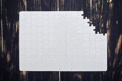 Puzzle with a missing part on wooden desk royalty free stock photography