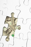 Puzzle with money. Puzzle missing one piece with money in the background of the empty space Royalty Free Stock Image