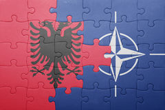 Puzzle with the national flag of albania and nato. Concept royalty free stock photo