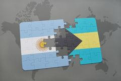 Puzzle with the national flag of argentina and bahamas on a world map background. Royalty Free Stock Photography