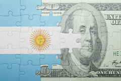 Puzzle with the national flag of argentina and dollar banknote Stock Images