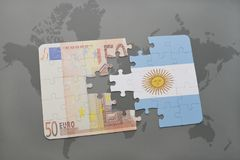 Puzzle with the national flag of argentina and euro banknote on a world map background. Royalty Free Stock Photos