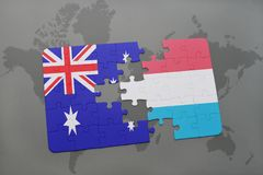 Puzzle with the national flag of australia and luxembourg on a world map background. Concept Stock Images