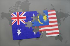 Puzzle with the national flag of australia and malaysia on a world map background. Royalty Free Stock Photos