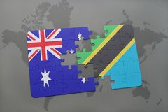 Puzzle with the national flag of australia and tanzania on a world map background. Stock Image