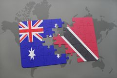 Puzzle with the national flag of australia and trinidad and tobago on a world map background. Royalty Free Stock Photography