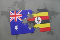 Puzzle with the national flag of australia and uganda on a world map background. Stock Photo