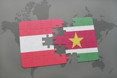 Puzzle with the national flag of austria and suriname on a world map background. 3D illustration Stock Photos