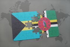 Puzzle with the national flag of bahamas and dominica on a world map background. 3D illustration royalty free stock photos