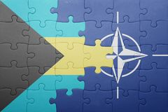 Puzzle with the national flag of bahamas and nato. Concept royalty free stock photography