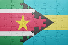 Puzzle with the national flag of bahamas and suriname. Concept Royalty Free Stock Photos