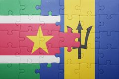 Puzzle with the national flag of barbados and suriname. Concept Stock Image