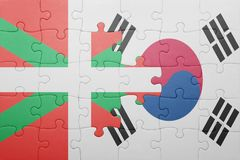 Puzzle with the national flag of basque country and south korea. Concept royalty free stock images