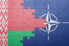 Puzzle with the national flag of belarus and nato. Concept royalty free stock photos