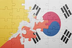 Puzzle with the national flag of bhutan and south korea. Concept royalty free stock photography