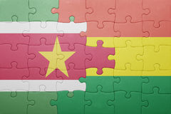 Puzzle with the national flag of bolivia and suriname. Concept Stock Photos