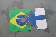 Puzzle with the national flag of brazil and finland on a world map background. Royalty Free Stock Photography