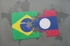 Puzzle with the national flag of brazil and laos on a world map background. 3D illustration royalty free stock photos