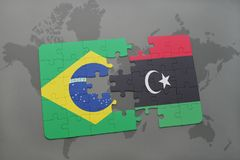 Puzzle with the national flag of brazil and libya on a world map background. 3D illustration Stock Photos
