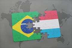 Puzzle with the national flag of brazil and luxembourg on a world map background. 3D illustration royalty free stock photos