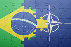Puzzle with the national flag of brazil and nato Royalty Free Stock Images