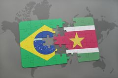Puzzle with the national flag of brazil and suriname on a world map background. 3D illustration Royalty Free Stock Photos