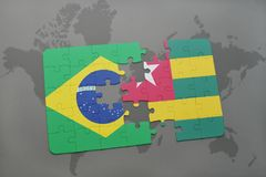Puzzle with the national flag of brazil and togo on a world map background. 3D illustration Stock Image