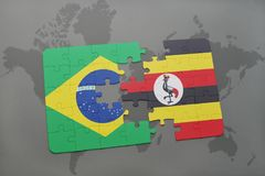 Puzzle with the national flag of brazil and uganda on a world map background. 3D illustration Stock Images