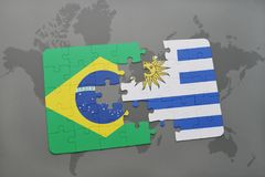 Puzzle with the national flag of brazil and uruguay on a world map background. 3D illustration Stock Photos