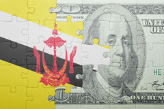 Puzzle with the national flag of brunei and dollar banknote Stock Image