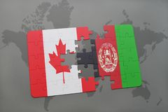 Puzzle with the national flag of canada and afghanistan on a world map background. Royalty Free Stock Images