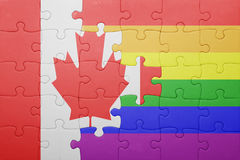 Puzzle with the national flag of canada and gay flag. Concept Royalty Free Stock Photo