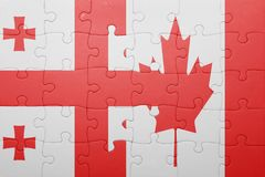 Puzzle with the national flag of canada and georgia. Concept Stock Photo