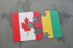 Puzzle with the national flag of canada and guinea on a world map background. Royalty Free Stock Photography