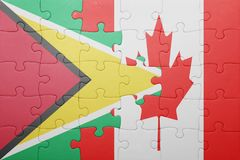 Puzzle with the national flag of canada and guyana. Concept Stock Image
