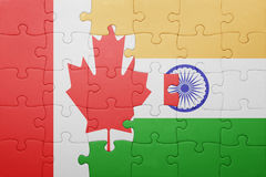 Puzzle with the national flag of canada and india. Cotncept Royalty Free Stock Photography